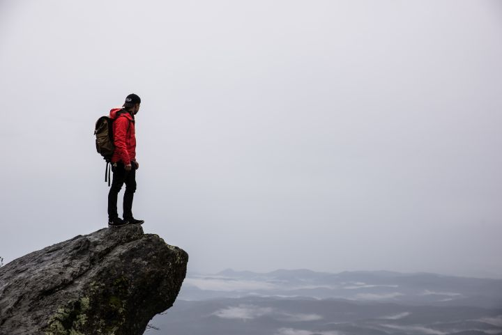 Tall man on a ledge with a backpack